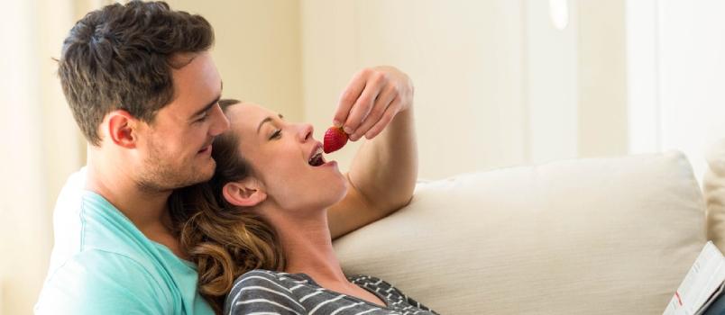 Couple romantique, hommes et femmes sur le canapé, femmes allongées sur la poitrine d'un homme, homme donnant des fraises dans la bouche d'une femme.