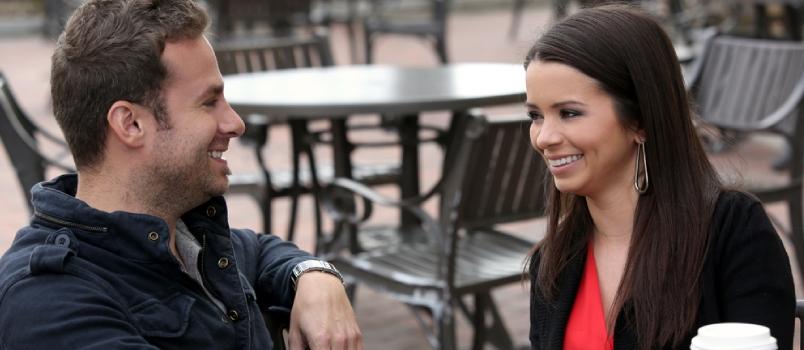 Hommes et femmes séduisants se regardant et souriant ensemble lors d'un concept de rencontre en plein air.