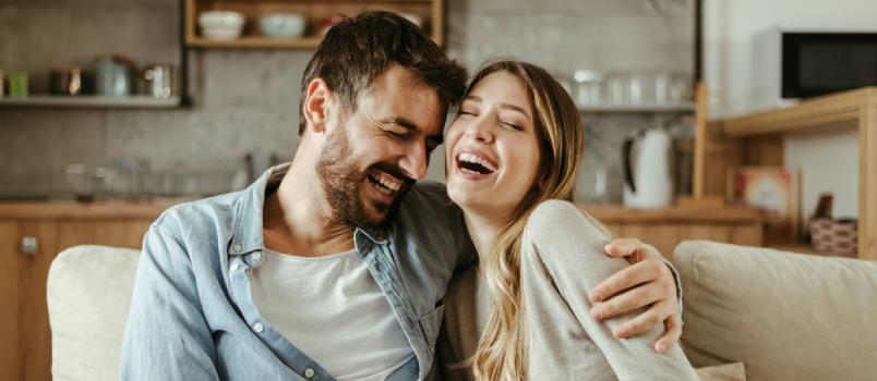 Iconique couple heureux riant ensemble sur le canapé à la maison.